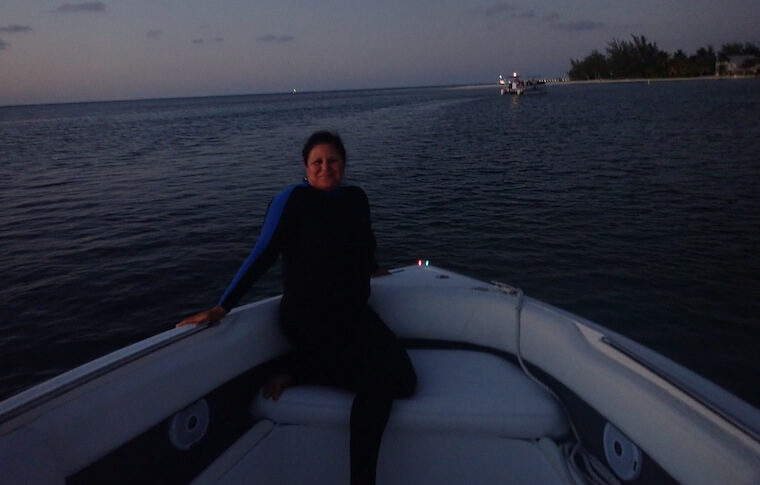 Woman sitting inside a boat at dusk