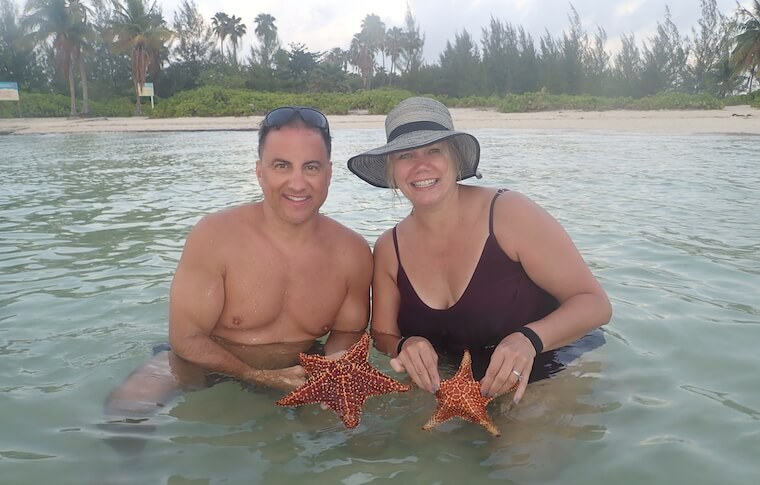 Man and woman each holding a starfish in Starfish Point